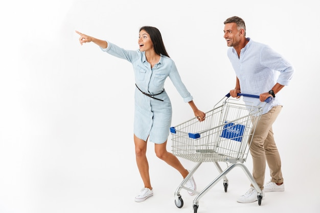 Cheerful couple running with a shopping cart