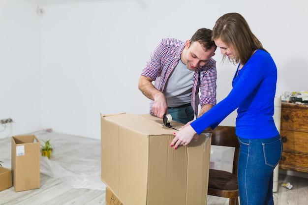 Cheerful couple sealing box