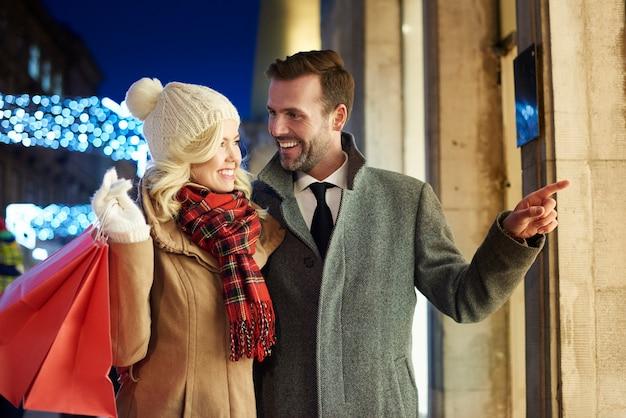 一緒に屋外で買い物をする陽気なカップル