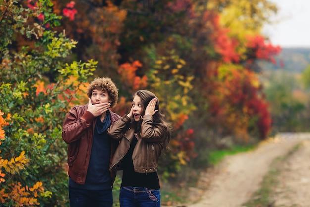 陽気なカップルは感情を示しています。革のジャケットとジーンズの男性と女性は、秋の木の背景に対して驚きを示しています。
