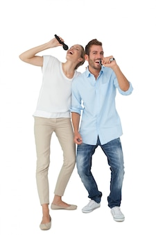 Cheerful couple singing into microphones