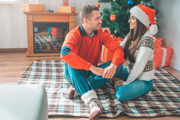 Cheerful couple sitting togethr on blanket on floor
