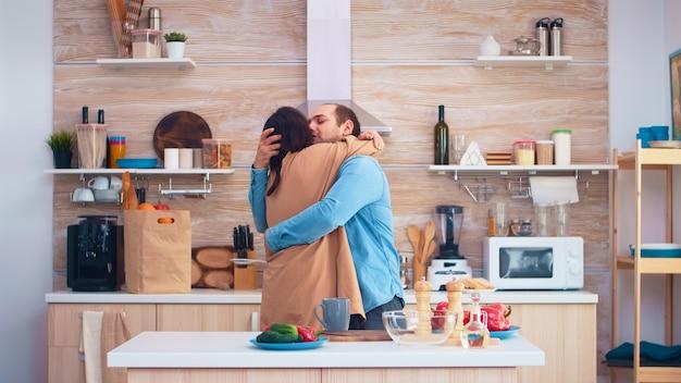 쾌활 한 커플 웃 고 부엌에서 춤입니다. 낭만적인 남편과 아내. 쾌활한 행복한 젊은 가족이 함께 춤을 춥니다. 즐거움을위한 재미있는 사랑 애정 로맨스 여가 낭만적 인 음악