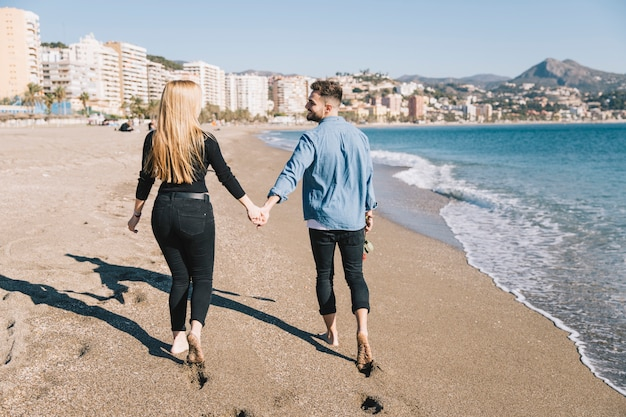 Cheerful couple strolling on beach in sunlight