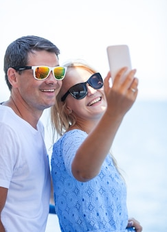 Cheerful couple in sunglasses taking mobile selfie