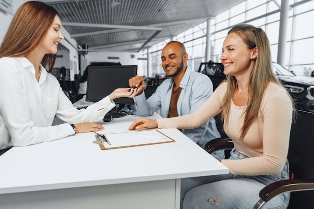 Cheerful couple taking keys of their new car in car dealership from saleswoman