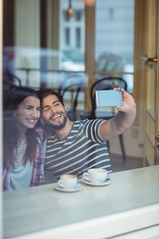 Cheerful couple taking selfie at cafe