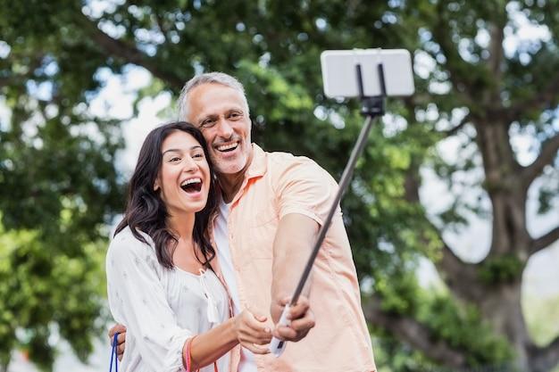 Cheerful couple taking selfie using monopod