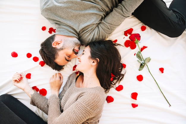 Cheerful couple touching noses on rose petals