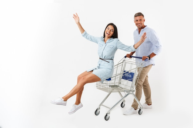 Cheerful couple walking with a shopping cart