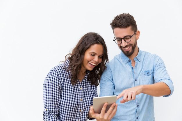 Веселая пара смотрит контент на планшете и смеется