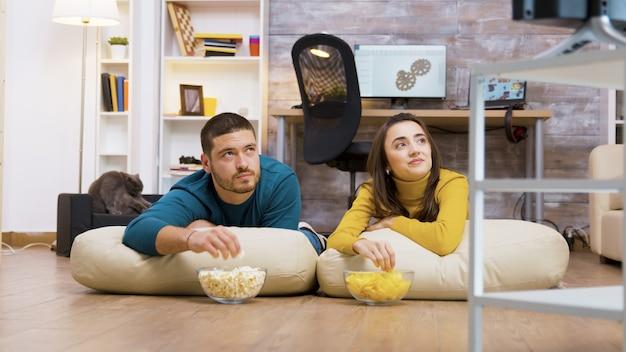 Веселая пара смотрит телевизор, сидя на подушках для пола, ест чипсы и попкорн со своей кошкой на заднем плане.