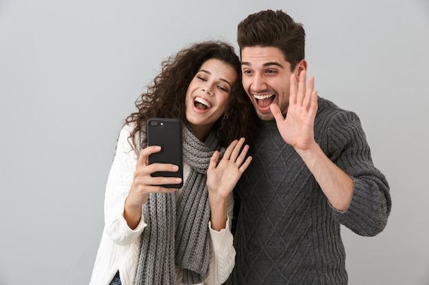 회색 벽 위에 고립 된 서 스웨터를 입고 명랑 커플, 화상 통화