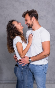 Cheerful couple in white hugging