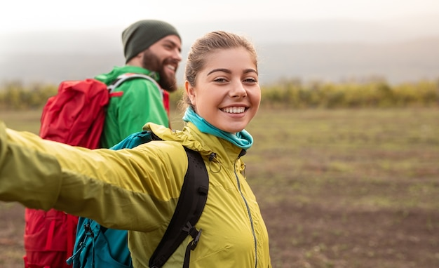 Cheerful couple with backpacks hiking in autumn nature