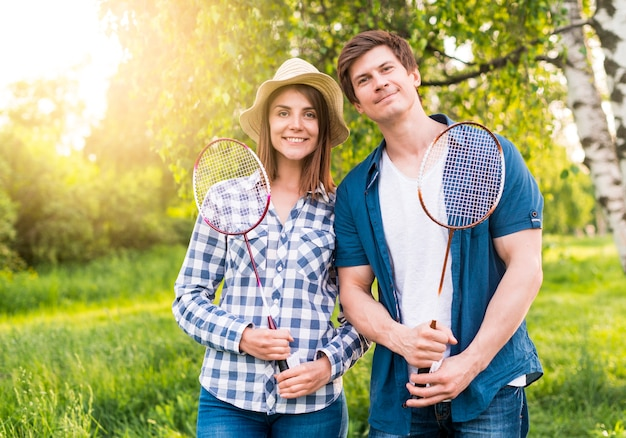 Cheerful couple with badminton rackets in park