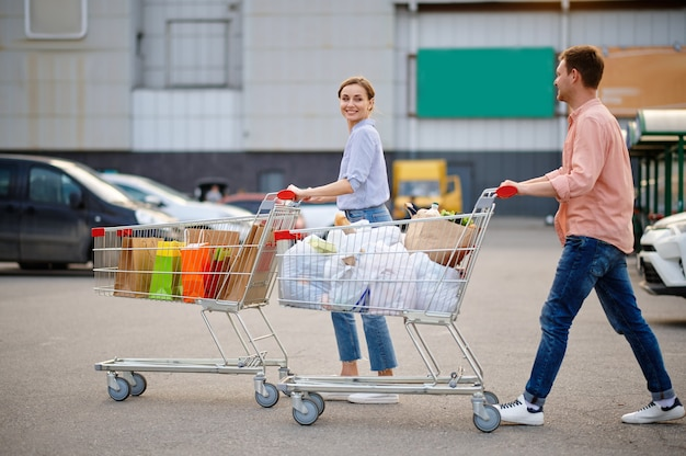 Cheerful couple with bags in carts on supermarket car parking. happy customers carrying purchases from the shopping center, vehicles on background