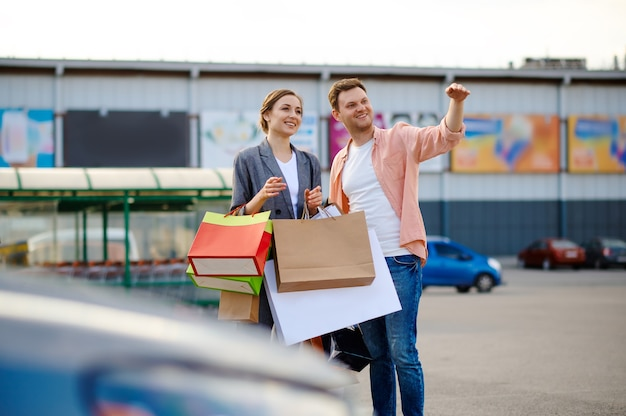 Cheerful couple with bags on supermarket parking
