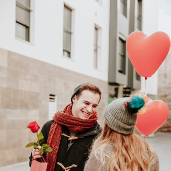 Cheerful couple with balloons and gifts