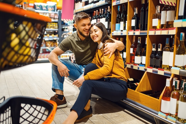 Cheerful couple with cart in grocery supermarket together