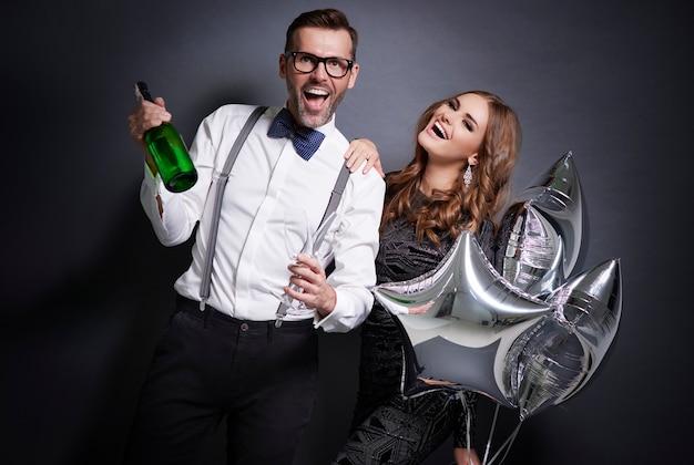 Веселая пара с шампанским празднует новый год