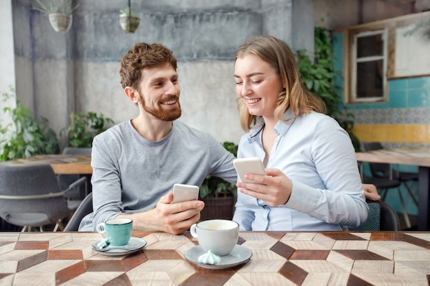 Cheerful couple with coffee and phone in cafe