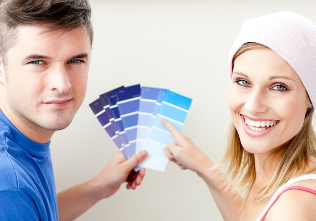 Cheerful couple with color samples for painting a room