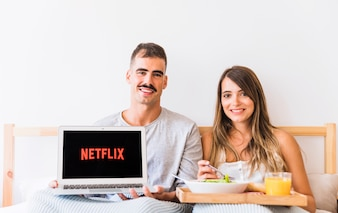 Cheerful couple with food showing Netflix logo