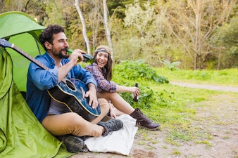 Cheerful couple with guitar drinking beer