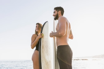 Cheerful couple with surfboards standing near sea