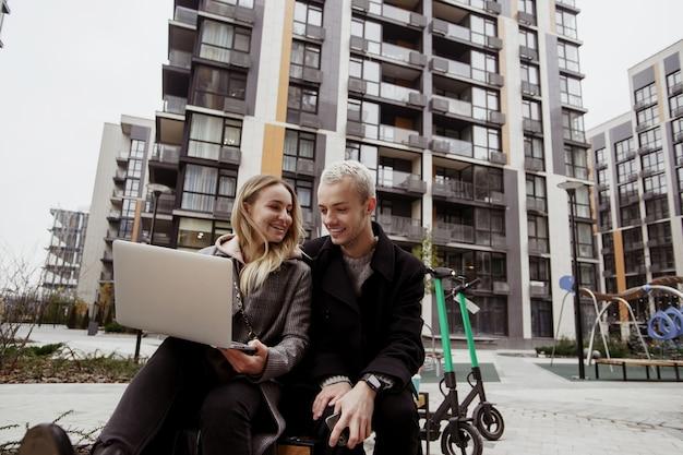 外で働く陽気なカップル。ノートパソコンを持って彼氏に面白い話をする若い魅力的な女性。彼のガールフレンドを聞いて笑っているカジュアルな服を着た男。彼らはベンチに座っています。