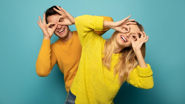 A cheerful couple in yellow sweaters are goofing around together, making glasses out of their hands and laughing together