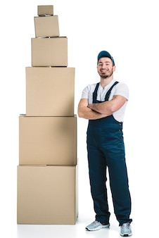 Cheerful courier near stack of boxes
