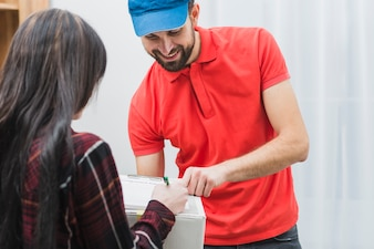 Cheerful courier pointing to clipboard for woman