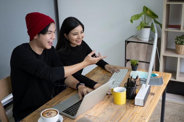 オフィスで一緒にプロジェクトについて話し合う陽気なクリエイティブな人々。