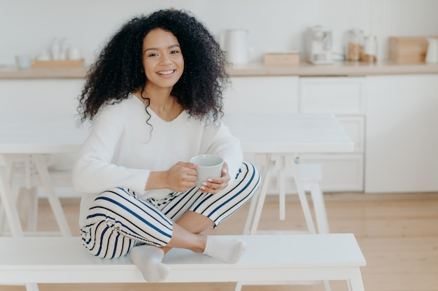 Cheerful curly african american woman sits in lotus pose at white bench sips tasty aromatic drink