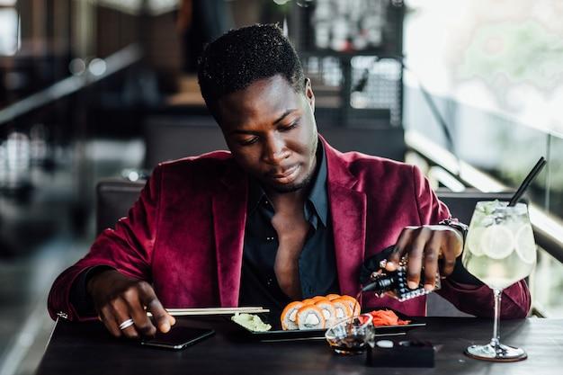 箸巻き寿司を持っている陽気な巻き毛のアフリカ人。中華料理の魚料理レストランテラス。