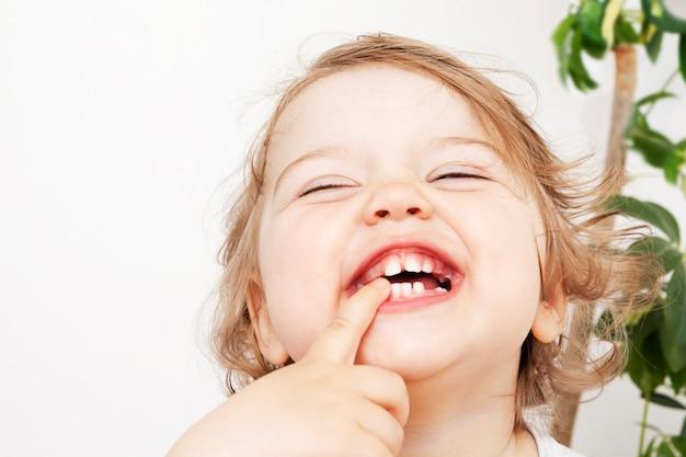 Веселый кудрявый малыш смеется очень весело. счастливый малыш дома. позитивное и радостное концептуальное фото