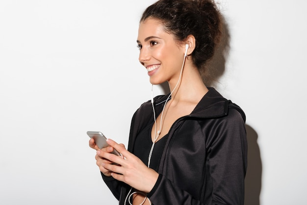 Cheerful curly brunette fitness woman listening music