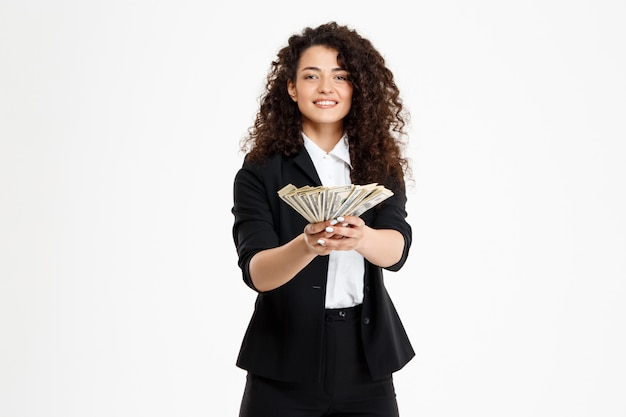 Cheerful curly business girl holding money