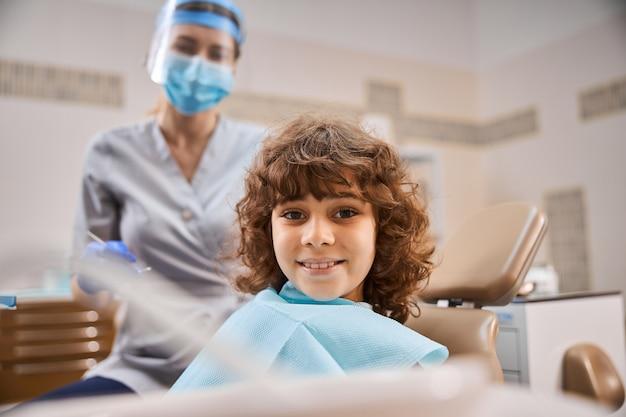 치과 진료소에서 의료 상담 중에 잘 보이는 쾌활한 곱슬 아이
