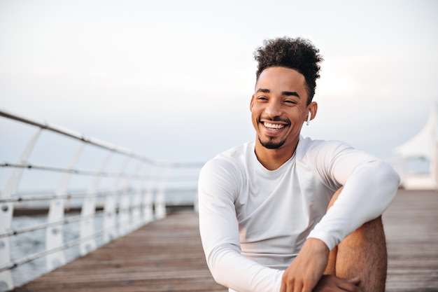 Cheerful curly dark-skinned man in white long-sleeved t-shirt smiles sincerely and rests near sea