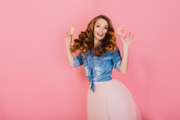 美味しいドーナツを持ってトレンディなスカートで陽気な巻き毛の女の子は、食事の終わりに喜ぶ。ピンクの背景に分離されたお菓子でポーズレトロな衣装で長い髪の女性をジャンプの肖像画