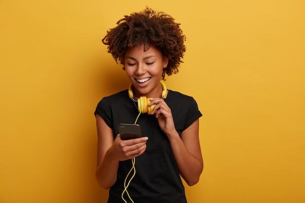 쾌활한 곱슬 소녀가 재생 목록에서 노래를 선택하고 목에 노란색 헤드셋을 착용합니다.