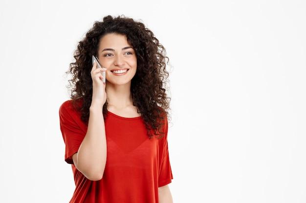 彼女の電話で話している陽気な巻き毛の女の子