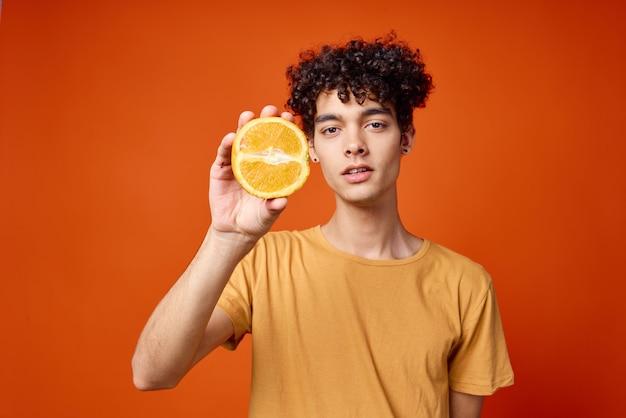 彼の手にオレンジを持った陽気な巻き毛の男フルーツライフスタイル