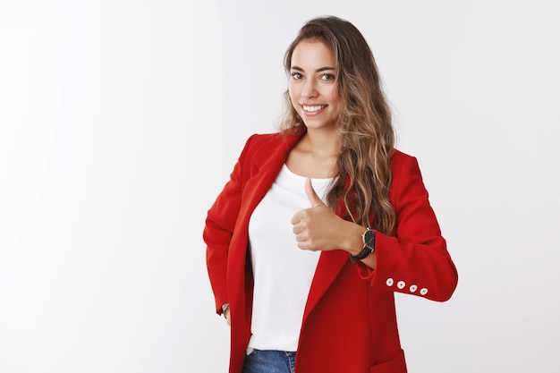 Веселая кудрявая кавказская женщина с белыми зубами улыбается в красной модной куртке, показывает большой палец вверх, как жест одобрения, одобрительно улыбается, поздравляет друга с отличным выбором, хорошая работа