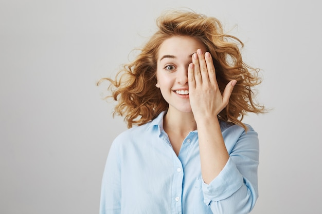 Веселая кудрявая девушка прикрывает половину лица и улыбается