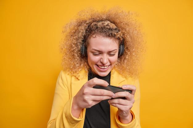 휴대 전화에서 비디오 게임에 중독 된 쾌활한 곱슬 머리 여자는 디스플레이에 집중된 무선 헤드폰을 사용하여 생생한 노란색 벽 위에 공식적으로 격리 된 게임을 즐깁니다.