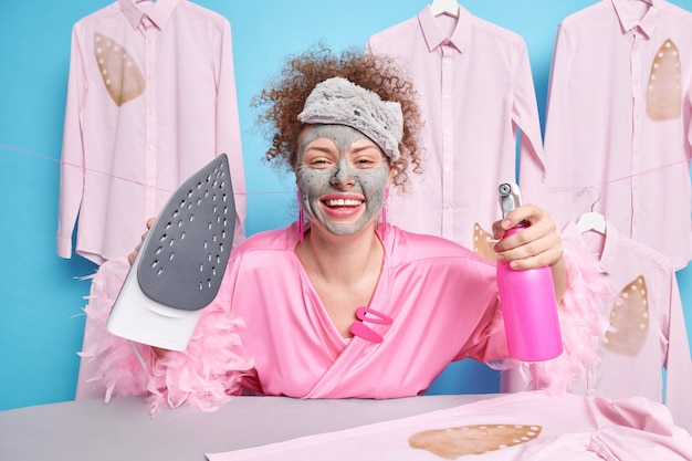 Cheerful curly haired woman smiles broadly dressed in domestic gown wears sleepmask applies beauty mask does domestic work sprays water on folded laundry while ironing spends weekend at home